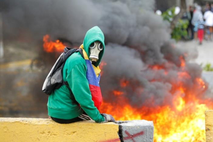 FILE PHOTO: Demonstrator sits next to a fire barricade on a street during a rally against Venezuela's President Nicolas Maduro in Caracas